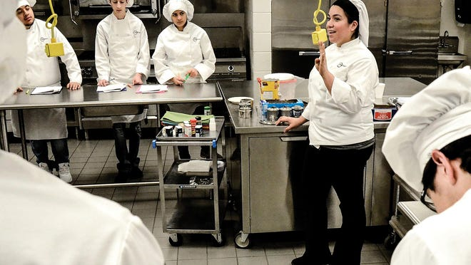 Elisabeth Maldonado, right, instructs her students on the steps they need to do during a past culinary arts class at Garden City High School.