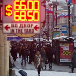 People walk past a display of a currency exchange office in St.Petersburg, Russia, on Jan. 27.