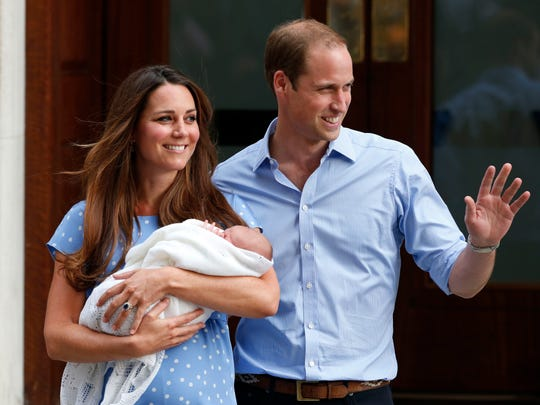 In this Tuesday, July 23, 2013 file photo, Britain's Prince William and Kate, Duchess of Cambridge hold George, the Prince of Cambridge, as they pose for photographers outside St. Mary's Hospital exclusive Lindo Wing in London.