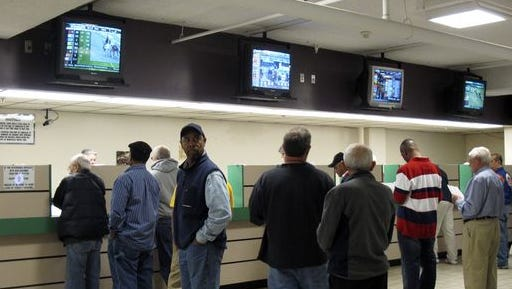 In this Oct. 21, 2011 photo, patrons line up to place bets at Freehold Raceway in Freehold, N.J. A non-binding question on the New Jersey ballot this November asks voters whether they favor legalizing sports betting at racetracks and casinos.