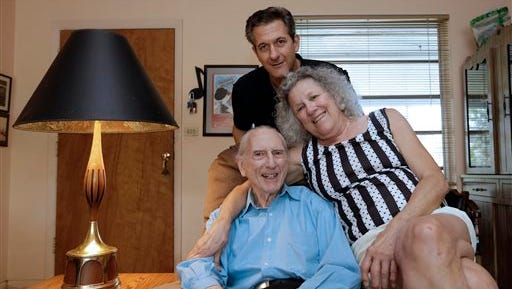 In this May 11, 2015 photo, Larry Karp, top, poses for photos with his parents, Al Karp, left, and Saundra, at their home in North Miami Beach, Fla. The trio performs old standards locally as the Karp Family to ease stress and help raise money to save their home from foreclosure. (AP Photo/Alan Diaz)