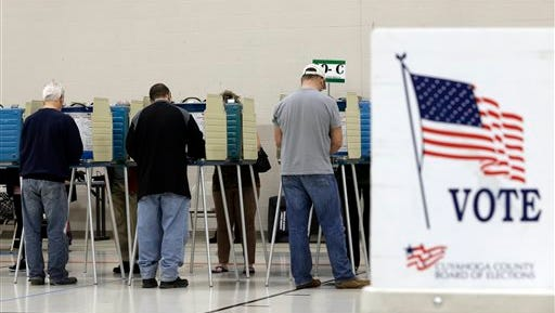 Voters cast their vote at the athletic wing of Orange High School Tuesday, Nov. 3, 2015, in Moreland Hills, Ohio. Election officials in two of Ohio's counties say lines of voters dwindled some after an early wave of Ohioans who cast their ballots early in the state's general election.