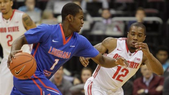 Louisiana Tech's Derric Jean (1)  tries to dribble past Ohio State's A.J. Harris (12) during the first half of an NCAA college basketball game Tuesday, Nov. 24, 2015, in Columbus, Ohio.