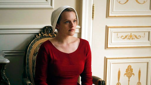 """This image released by Hulu shows Elisabeth Moss as Offred in a scene from, """"The Handmaid's Tale,"""" premiering Wednesday on Hulu with three episodes. The remaining seven hours will be released each Wednesday thereafter."""
