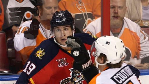 Florida Panthers' Scottie Upshall (19) watches the puck as Philadelphia Flyers' Sean Couturier (14) grabs it during the second period of the NHL hockey game in Sunrise, Fla., Monday, Nov. 25, 2013. (AP Photo/J Pat Carter)
