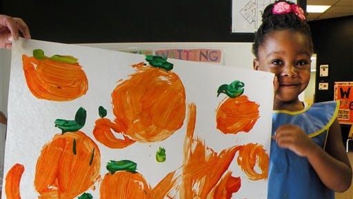 Oluwafunto Akinnurele holds a picture of pumpkins stolen from the Child Development Center at Eastern New Mexico University in Portales, N.M. Officials say the pumpkin patch was raided sometime over the weekend after students had worked for months growing the pumpkins.
