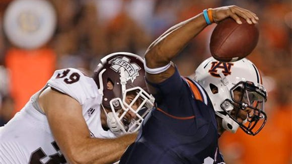 Mississippi State linebacker Richie Brown (39) sacks Auburn quarterback Nick Marshall (14) in the second half of an NCAA college football game in Auburn, Ala., Saturday, Sept. 14, 2013. Auburn won 24-20. (AP Photo/Dave Martin)