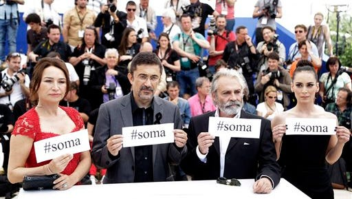 """From left, actress Demet Akbag, director Nuri Bilgle Ceylan, actor Haluk Bilginer and actress Melisa Soezen pose for photographers with signs reading """"soma,"""" a reference to Turkey's worst mining incident in which hundreds of miners were killed earlier this week in Soma, Turkey, during a photo call for 'Winter Sleep' at the 67th international film festival, Cannes, southern France, Friday."""