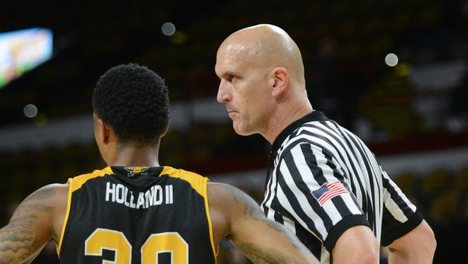 Referee D.J. Carstensen, a Milwaukee native, talks with Northern Kentucky guard Lavone Holland II while working a Horizon League game this season at the UW-Milwaukee Panther Arena.