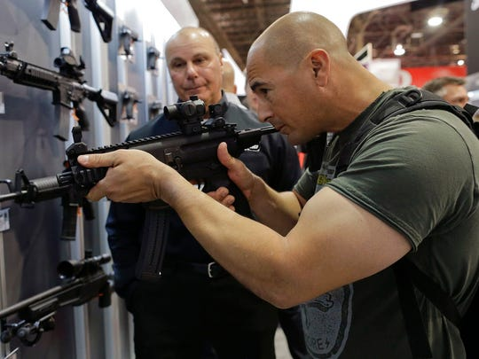 In this Jan. 14, 2014, file photo, John Montenegro of the Los Angeles Police Department S.W.A.T. team, examines a Sig Sauer MPX-K short barrel submachine gun during the Shooting Hunting and Outdoor Trade Show in Las Vegas.