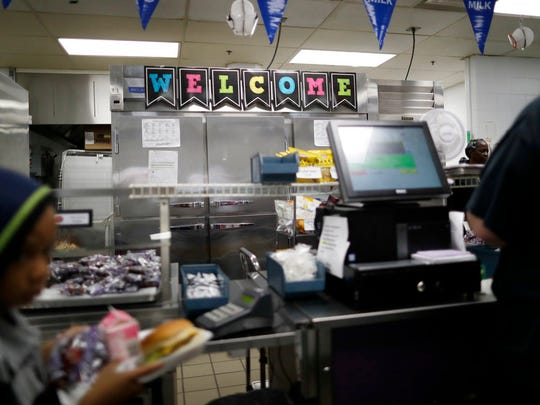 A sign in the cafeteria welcomes children at the John G. Carlisle Elementary School in Covington, Ky., on April 27, 2018. After agents arrested the parent of two students at the school, one of the students told an interpreter that they only had eggs to eat in the house. (AP Photo/Gregory Bull)