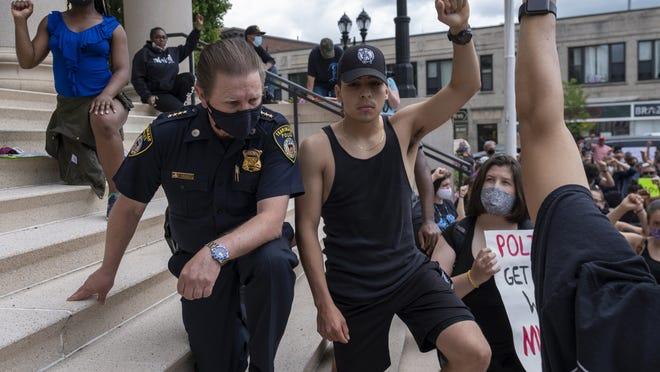 Framingham Police Chief Steven Trask kneels next to Kevin Luna Torres, of Framingham, in front of the Memorial Building in Framingham, during the Black Lives Matter protest, June 7, 2020.