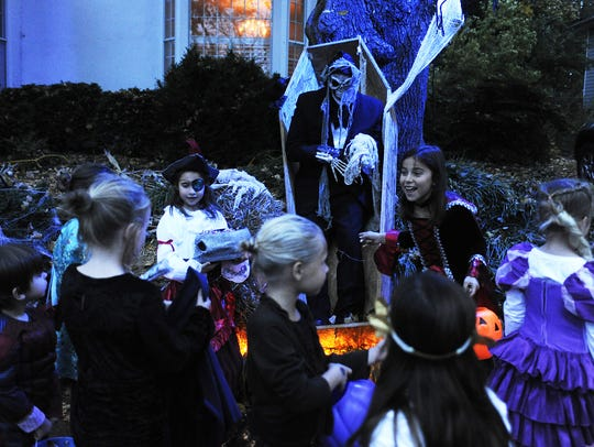 Trick-or-treaters laugh and scream as a skeleton in