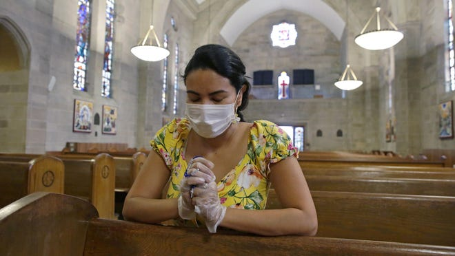 Parishioner Laura Sanchez holds a rosary while she prays wearing mask and protective gloves at Saint Jude Melkite Greek Catholic Church in Miami on Easter Sunday, April 12