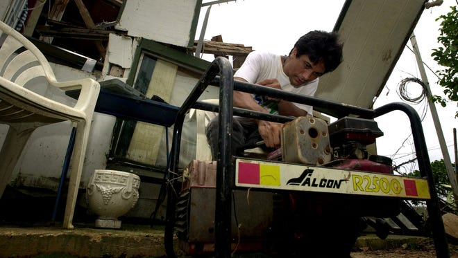 Andrew Galimba fixes a generator in front of his heavily damaged Dededo house following Typhoon Chata'an in July 2002.