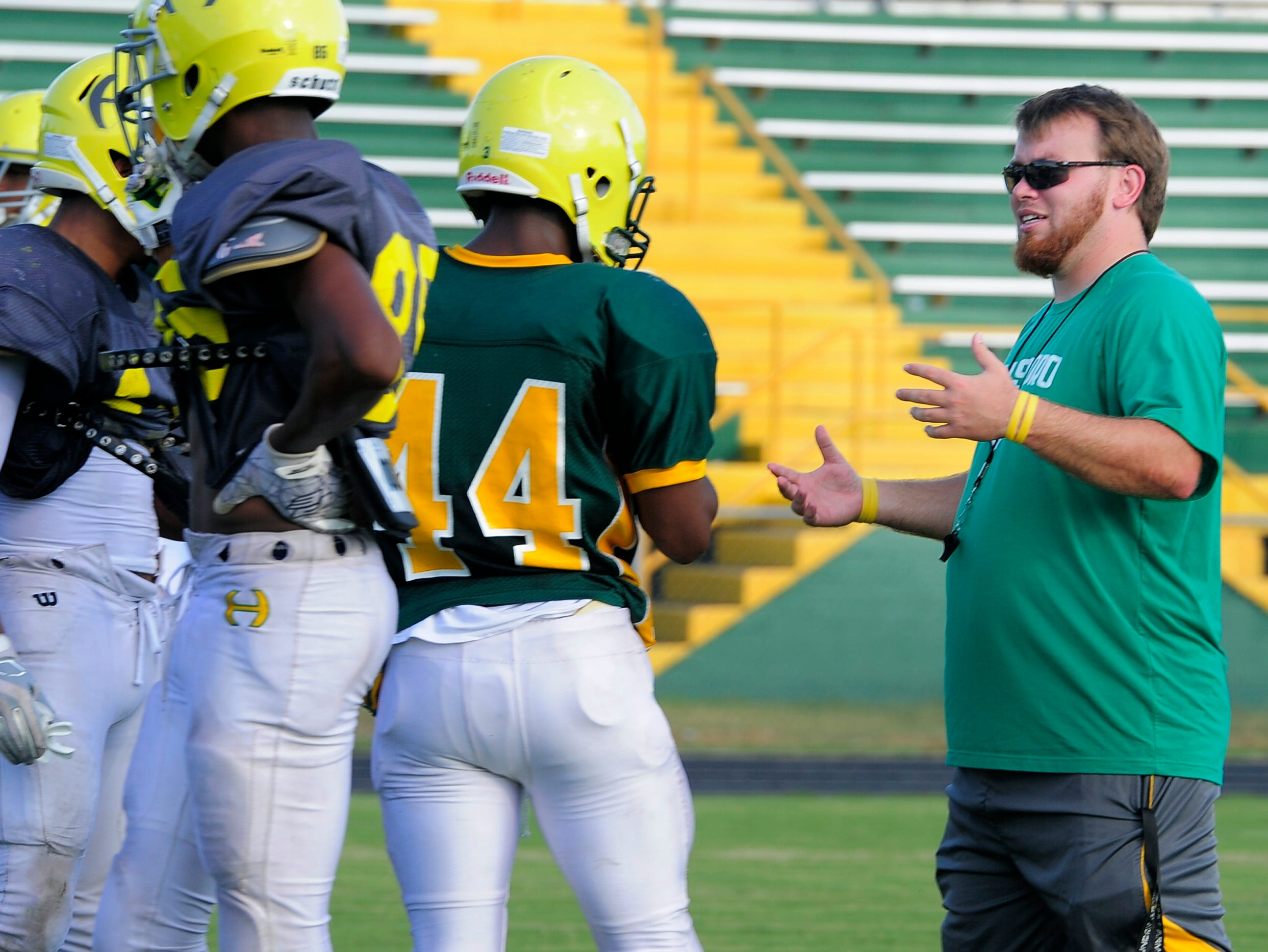Hillsboro assistant football coach Dustin Lopez talks with his players during a practice Tuesday in Nashville. The school's statisticians are using an app called iscore to compile live stats during a game.