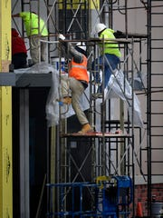 Construction workers climb scaffolding at the at the new Shops at Abilene Village in the 3500 block of South Clack Street Dec. 29.