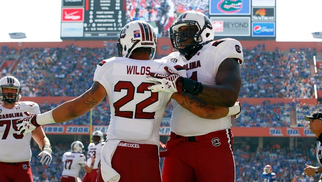 South Carolina Gamecocks running back Brandon Wilds (22) is congratulated by offensive tackle Brandon Shell (71) and teammates after he scored a touchdown against the Florida Gators  during the first quarter at Ben Hill Griffin Stadium.