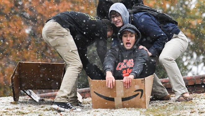 Clemson University student Jesse Russell, a foreign exchange student from Australia, reacts as Matt Troy, right, and Morgan King, left, push him on his cardboard box down a hill in Clemson on Friday. The three decided to use the boxes to sled down a small hill nearby, on the last day of classes before final exam week starts on Monday.