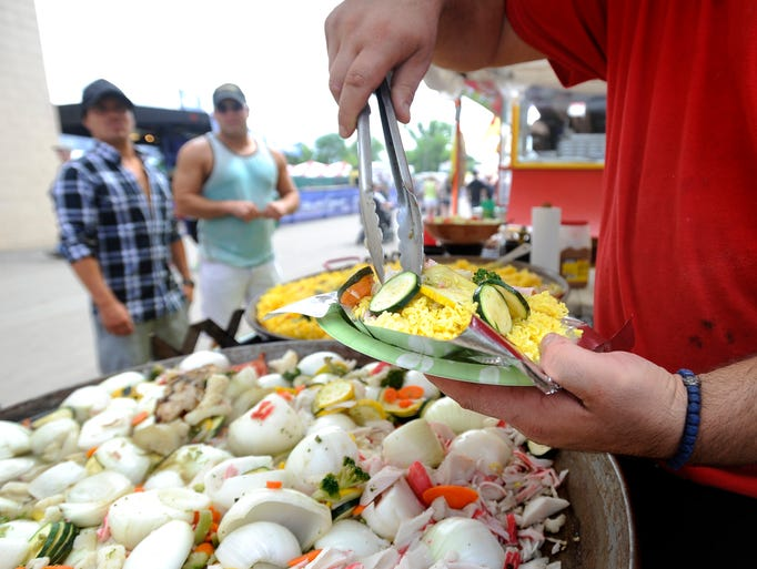 Duscan Maksimovic dishes up streamed vegetables and rice to go with crab cakes for Dane Keller and Aaron Hultgren during the Sioux Empire Fair in Sioux Falls, S.D., Sunday, Aug., 10, 2014.