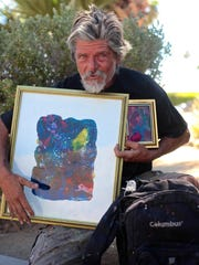 Street artist, Robert Staich, also known as 'Scratch' holds a few of his paintings on a hot morning in Palm Springs on Monday, June 1.