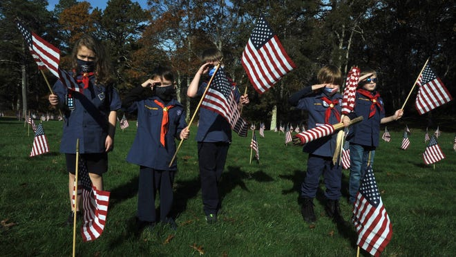 Cub Scouts from Pack 11 in Plymouth pause from flag planting for a flag salute at the Bourne National Cemetery, where a large group of volunteers showed up to place flags on all the graves to honor them for Veteran's Day.