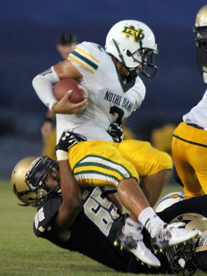 Xavier College Prep's Justin Sykes tackles Notre Dame's Manny Guerrero during the first half of the game at Xavier College Prep in Palm Desert on Friday, August 28, 2015.