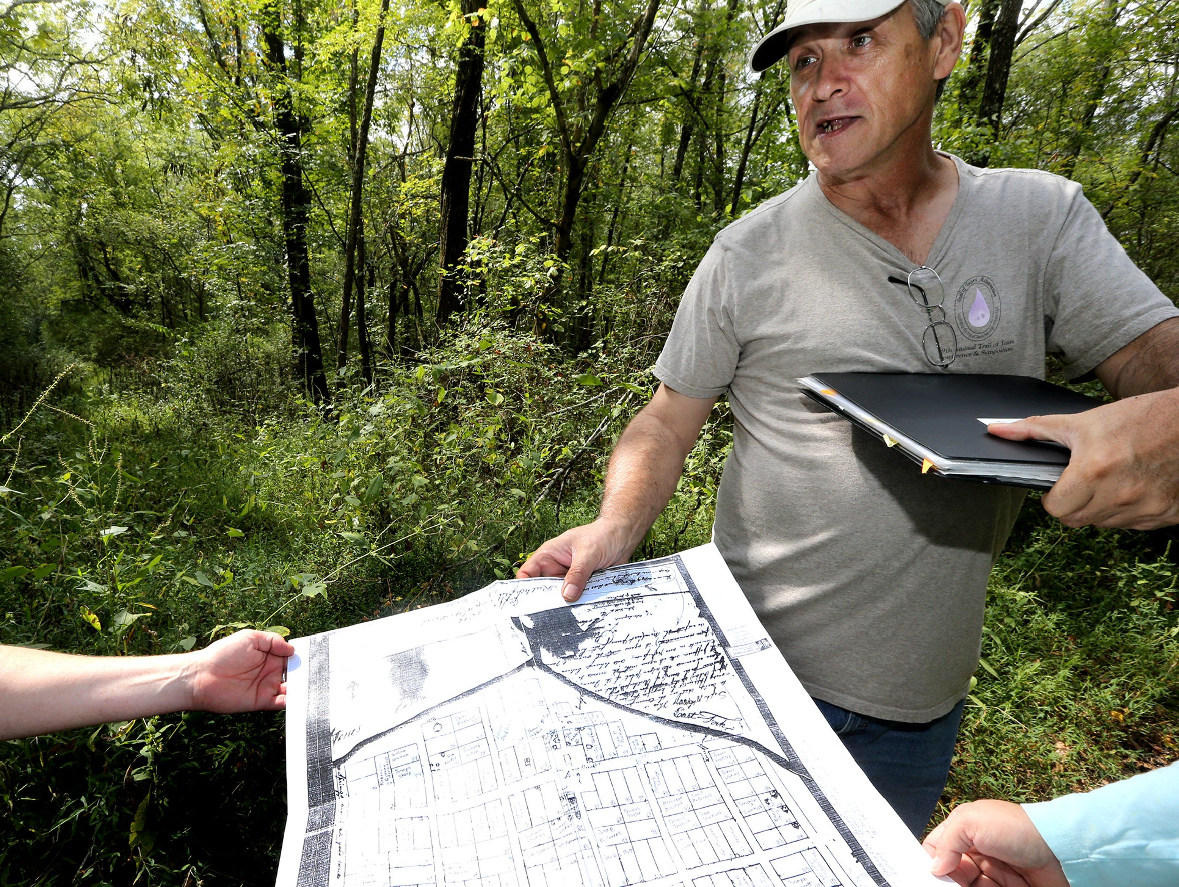 Pat Cummins shows an old map of Jefferson as he stands