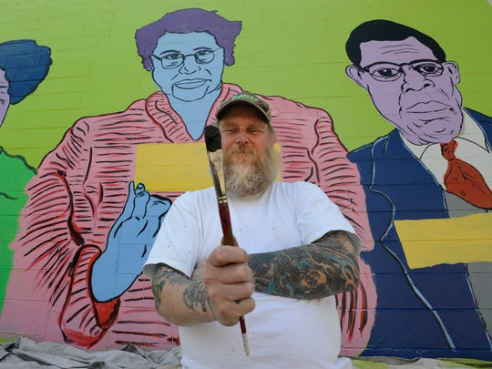 Tim Kerr paints a mural near the skate park in downtown
