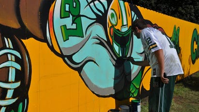 Black Creek artist Spencer Young works on his Eddie Lacy painting on a fence near Lambeau Field in September.