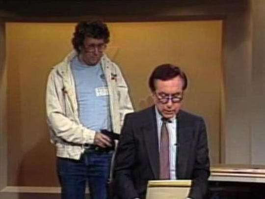 This Aug. 20, 1987, image made from video shows an intruder with a gun, as journalist David Horowitz is taken hostage during a live broadcast of Channel 4 Los Angeles. Horowitz remained calm and read the gunman's statements on camera, but the station had cut the broadcast without the gunman becoming aware of that fact. The longtime consumer journalist has died at age 81, his wife told NBC4.