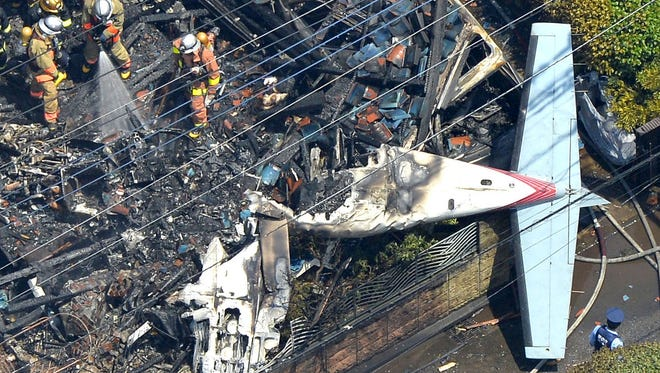 The wreckage of a plane is seen at a crash site in the suburbs of Tokyo, Sunday, July 26, 2015.