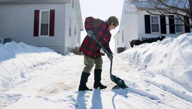 """Linda Briody clears off her North Side Evansville driveway for the second time in as many days Tuesday afternoon. """"It wasn't as bad this time,"""" Briody said. """"Sunday's snow had ice under it."""""""