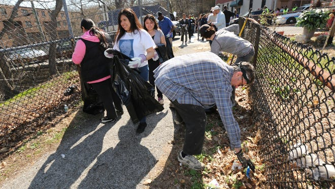 Volunteers Glenn Madison and Mayte Vazquez from Yonkers gather trash as others make their way out, for the 4th annual cleanup of the Old Croton Aqueduct State Historic Park in Yonkers, April 18, 2015. Hundreds of people volunteered to cleanup the trail, east and west of Walnut Street.