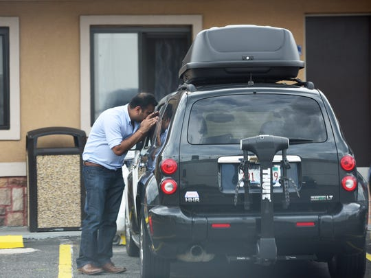 An employee of the Travelodge checks the inside of a car Chevy HHR in black that is apparently belonging to singer Sinead O'Connor, photographed at the Travelodge in S. Hackensack on August 8th 2017.