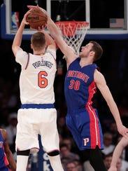 Knicks forward Kristaps Porzingis is fouled while shooting by Pistons forward Jon Leuer.