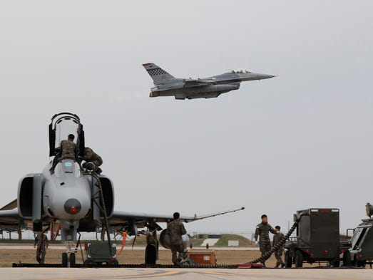 A U.S. Air Force F16 fighter (top) takes off at the