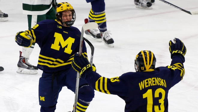 Michigan's Dexter Dancs, left, celebrates his goal with Zach Werenski (13) during the first period of an NCAA college hockey game against Michigan State, Friday, March 13, 2015, in East Lansing, Mich.