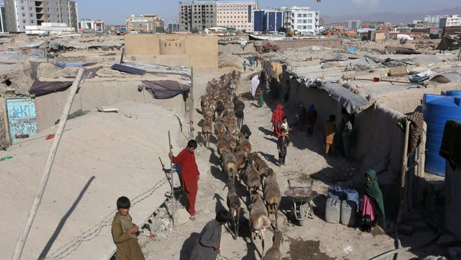 In this Monday, May 30, 2016 file photo, an afghan boy shepherd walk their sheep near a temporary housing in Kabul, Afghanistan.