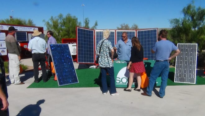 People look at solar panels.