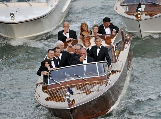 Now sit right back and you'll hear a tale, a tale of the wedding nobody saw coming: The SS Clooney navigates Venice's Grand Canal en route to the Oscar winner's marriage to British human-rights lawyer Amal Alamuddin. Also aboard: Clooney's newsman dad Nick (fourth from left) and Amal's dad Ramzi (to Clooney's right.)