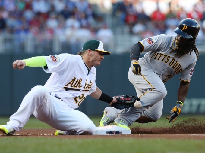 National League outfielder Andrew McCutchen, of the Pittsburgh Pirates, steals third base as American League Josh Donaldson, of the Oakland Athletics, tries to make the tag during the first inning of the MLB All-Star baseball game, Tuesday, July 15, 2014, in Minneapolis. (AP Photo/Jim Mone)