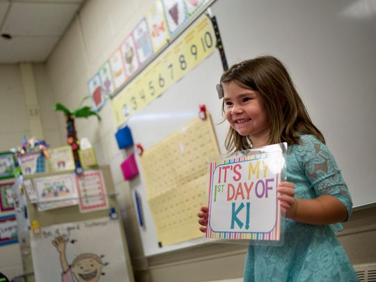 Kindergarten student Kylee Kramer, 5, holds a sign for a picture on her first day of school Tuesday, September 6, 2016 at Keewahdin Elementary School in Fort Gratiot.