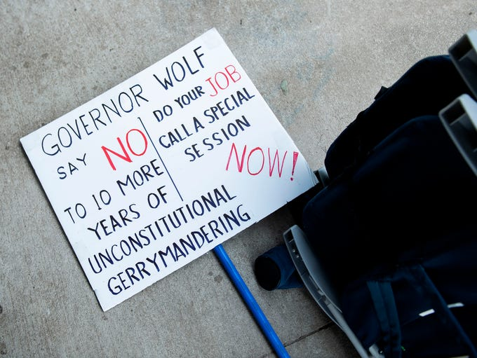 A sign rests on the ground prior to protesters with