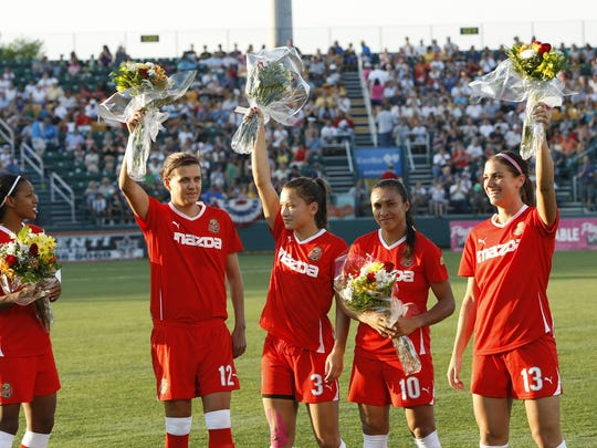 WNY Flash players who were in the 2011 World Cup, from left, Candace Chapman (Canada), Christine Sinclair (Canada), Ali Riley (New Zealand), Marta (Brazil), and Alex Morgan (USA), thank the crowd prior to a Women's Professional Soccer match against magicJack that drew 15,404 fans to Sahlen's Stadium in July of 2011.