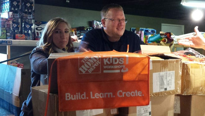 Home Depot Assistant Manager Kayla Cantrell and Manager Tim Capps deliver wooden building kits and aprons to Christmas Wish for filling Christmas wishes for children in the area.