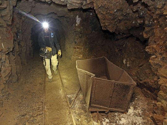 "In this Aug. 14, 2018, photo, Jeremy MacLee walks through a mine near Eureka, Utah. Underneath the mountains and deserts of the U.S. West lie hundreds of thousands of abandoned mines. Still, not everyone wants to see the mines closed. ""Nobody has walked the path you're walking for 100 years,"" said MacLee, who uses old mining documents and high-tech safety equipment to find and explore forgotten holes, mostly in Utah. He also lends his expertise to searches for missing people."