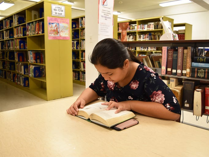 "Danielle Garcia, 12, reads ""Harry Potter and the Half-Blood"