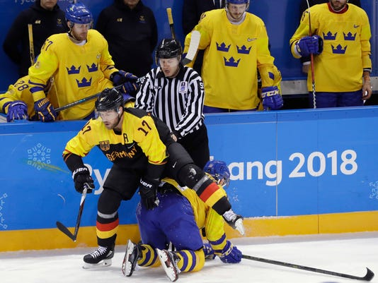 Marcus Kink (17), of Germany, climbs over Joakim Lindstrom (10), of Sweden, during the third period of a preliminary round men's hockey game at the 2018 Winter Olympics, Friday, Feb. 16, 2018, in Gangneung, South Korea. Sweden won 1-0. (AP Photo/Matt Slocum)