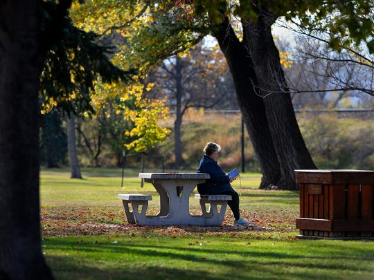 A local resident enjoys the relaxing quietude of a warm fall day at Gibson Park.